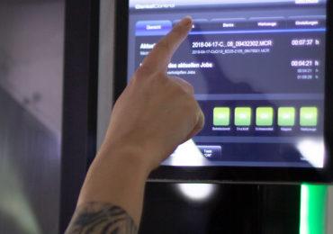 Hand einer Technikerin, die zur Zeit das Display einer Fräsmaschine bedient.